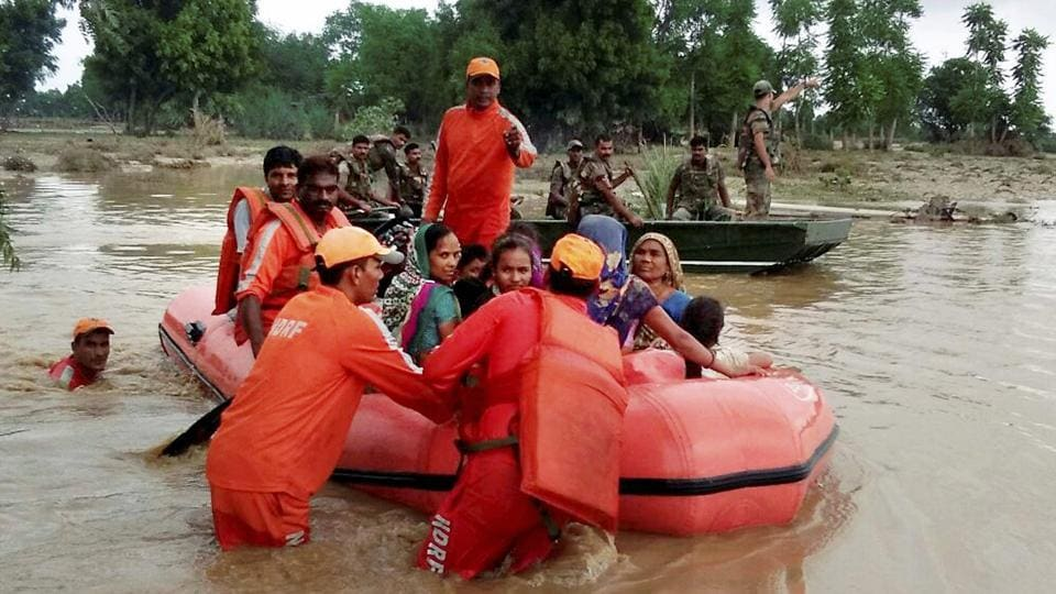 ANational Disaster Response Force team rescues flood-hit people at a village in Banskantha district on Wednesday.