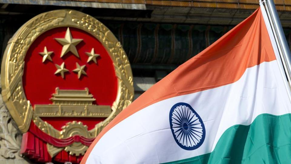 An Indian national flag is flown next to the Chinese national emblem.