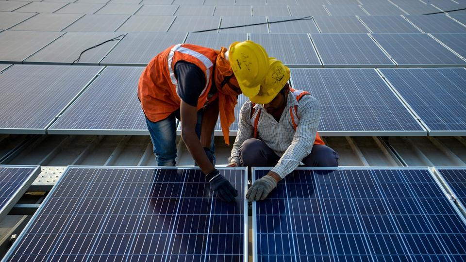 Labourers install solar panels at a site in Greater Noida, near New Delhi.