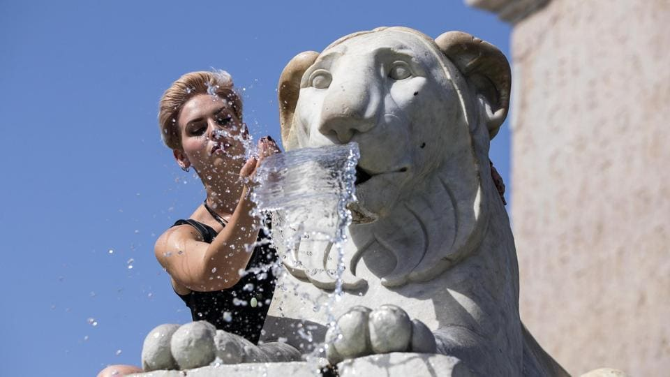 A woman cools off in a fountain at Piazza del Popolo in Rome, Italy on Thursday.