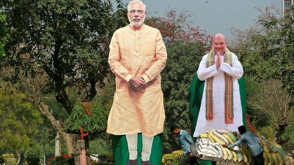 Giant cardboard cut outs of Prime Minister Narendra Modi and Amit Shah are displayed in New Delhi.