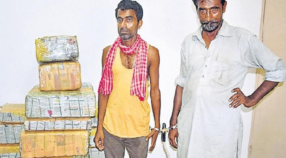 The arrested truck driver and cleaner with the seized contraband.