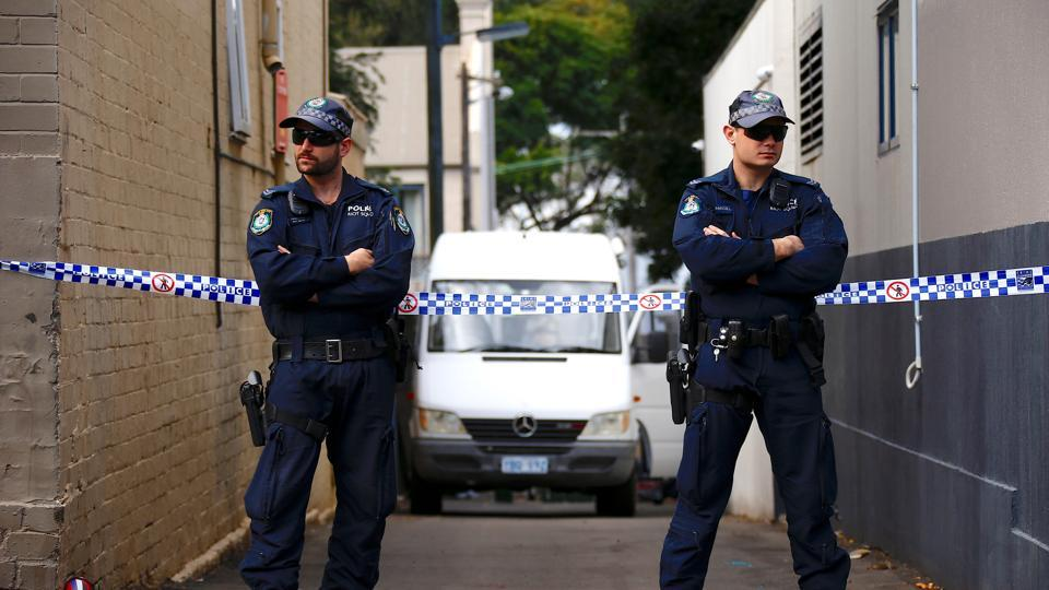 FILE PHOTO - Police officers block a small alley where police vans are parked at a home being searched after Australian counter-terrorism police arrested four people in raids late on Saturday across several Sydney suburbs in Australia, July 30, 2017.