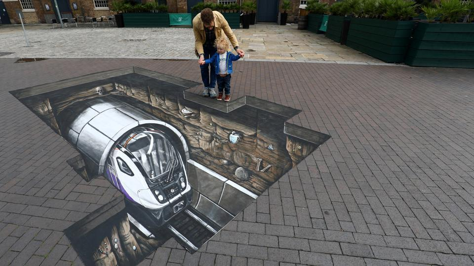 Mike Clueless and son Elliot pose by a piece of Crossrail themed 3D artwork during a photocall at the Museum of London Docklands in London, Britain. (REUTERS)