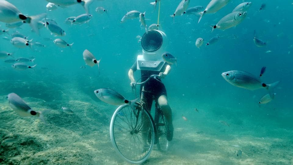 A woman dives and pretends to ride a bike in Underwater Park in Pula, Croatia. (REUTERS)