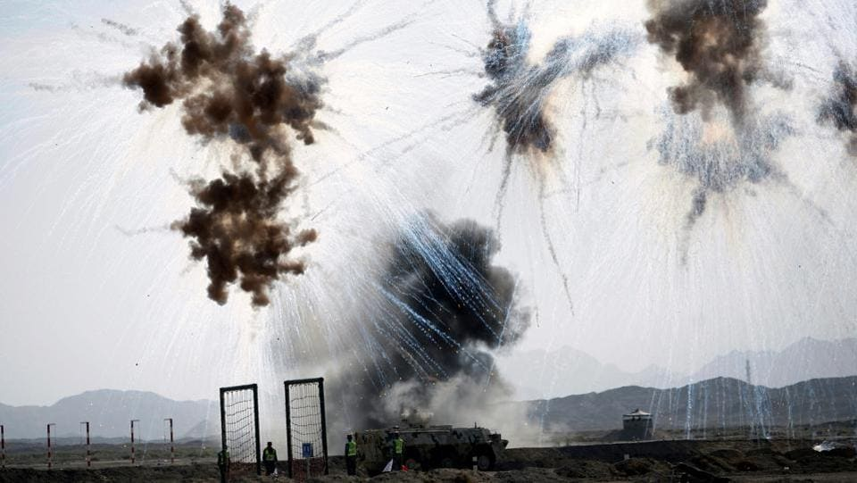 Chemical defense soldiers drive past a bombed position during Safe Environment competition, part of the International Army Games 2017 in Korla, Xinjiang Uighur Autonomous Region, China. (Wang Xiaojun  / REUTERS)