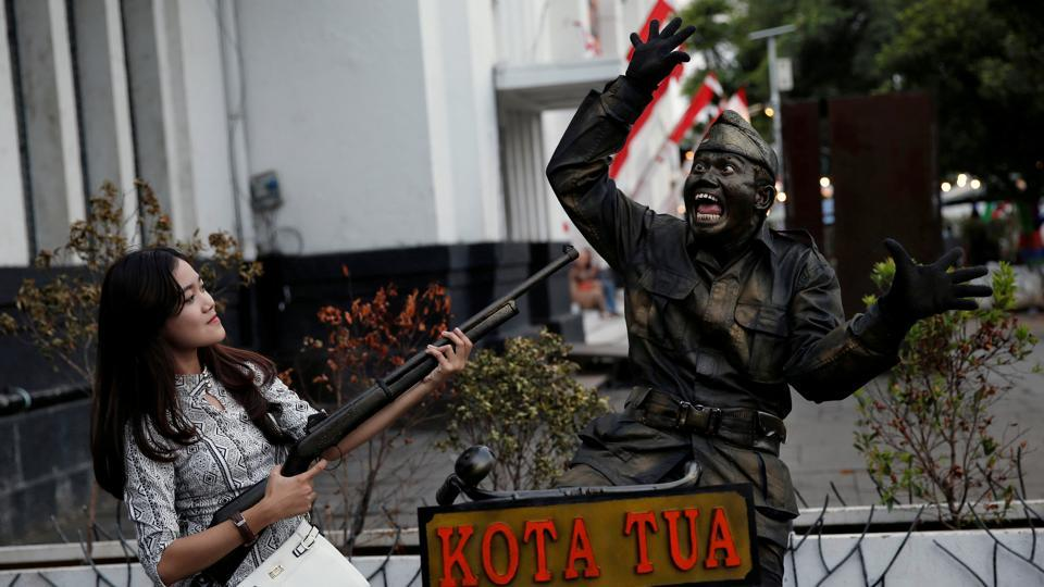 A tourist poses with a street performer dressed as an Indonesian soldier in Jakarta's Old Town compound, a popular tourist spot in Jakarta, Indonesia. (/Beawiharta / REUTERS)
