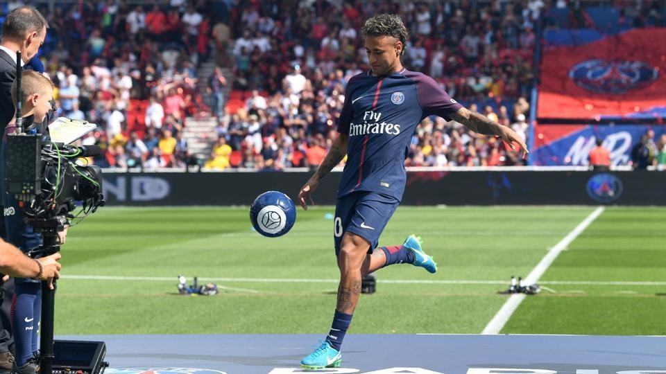 Paris Saint-Germain's Brazilian forward Neymar plays with a ball on stage during his presentation to the fans at the Parc des Princes stadium in Paris on August 5.