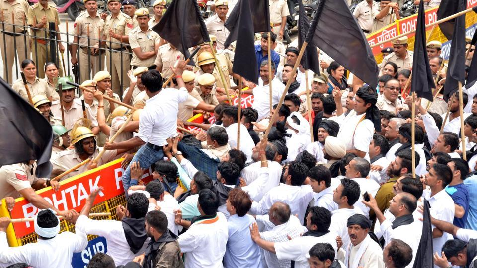 Congress workers trying to cross a police barricade during a protest in Rohtak on Friday.
