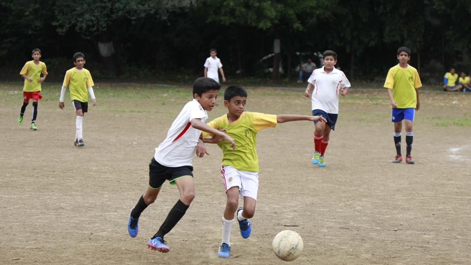Players of Millennium National school, (yellow) & Vikhe Patil Memorial School (white) in action during the football match at SSPM college ground in Pune on Friday.
