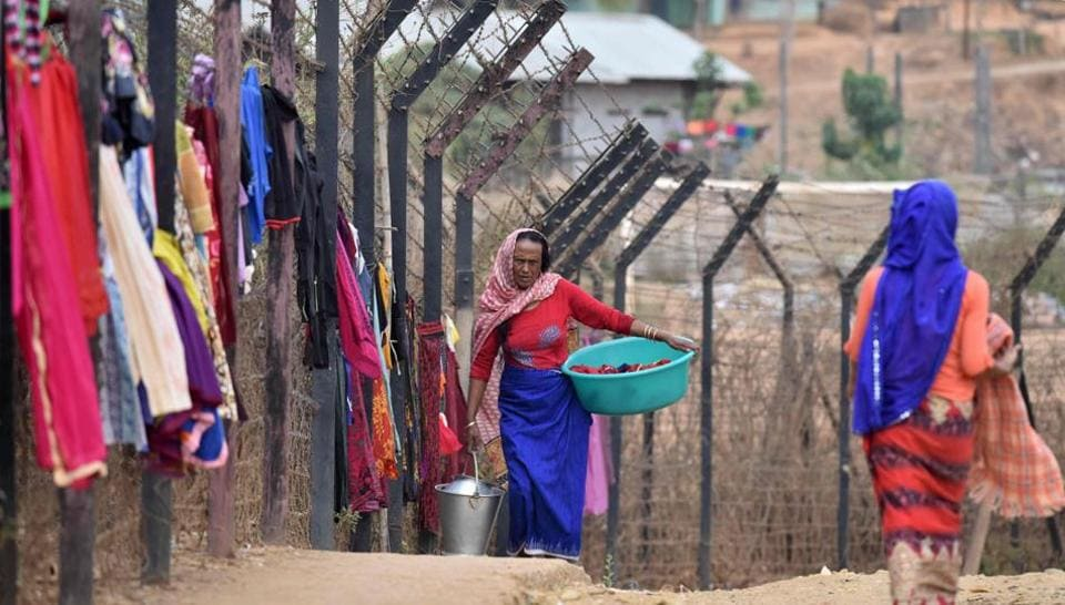 A woman carries her laundry past washing hanging up to dry on the India-Myanmar border fencing at Moreh, some 120 kms from Imphal, the capital city of Manipur on March 10, 2017. India and Myanmar share a 1,624-kilometer (1,009 miles)-long border. Border fencing is still not completed in India-Myanmar border.