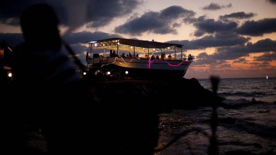 Palestinians are seen aboard 'Lolo Rose' ship which has become a popular restaurant, on a beach in Gaza City . (REUTERS)
