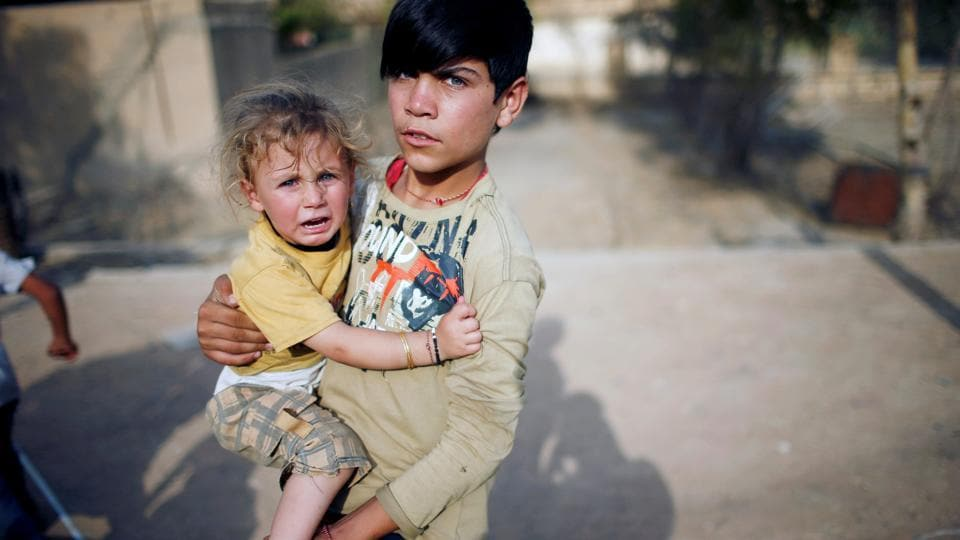 A Yazidi boy holds his sister in a playground in Sinjar region, Iraq. (Suhaib Salem  / REUTERS)