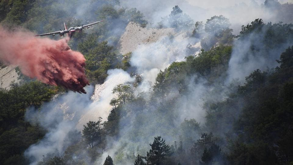 A plane drops flame retardant to put out a fire in Rigaud, north of Nice, southeastern France. France has been battling for several weeks huge fires near beaches popular with tourists on the Cote d'Azur, forcing the evacuation of people.  (Yann COATSALIOU / AFP)