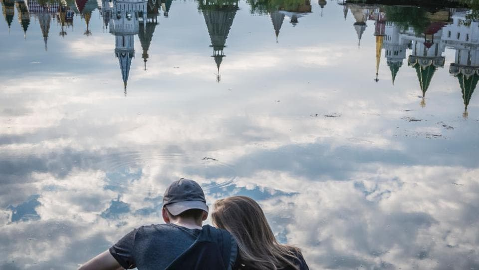 A couple enjoys the view of the ethnographic and amusement center Kremlin in Izmailovo reflected in the Serebryano-Vinogradnii lake in Moscow . (AFP)