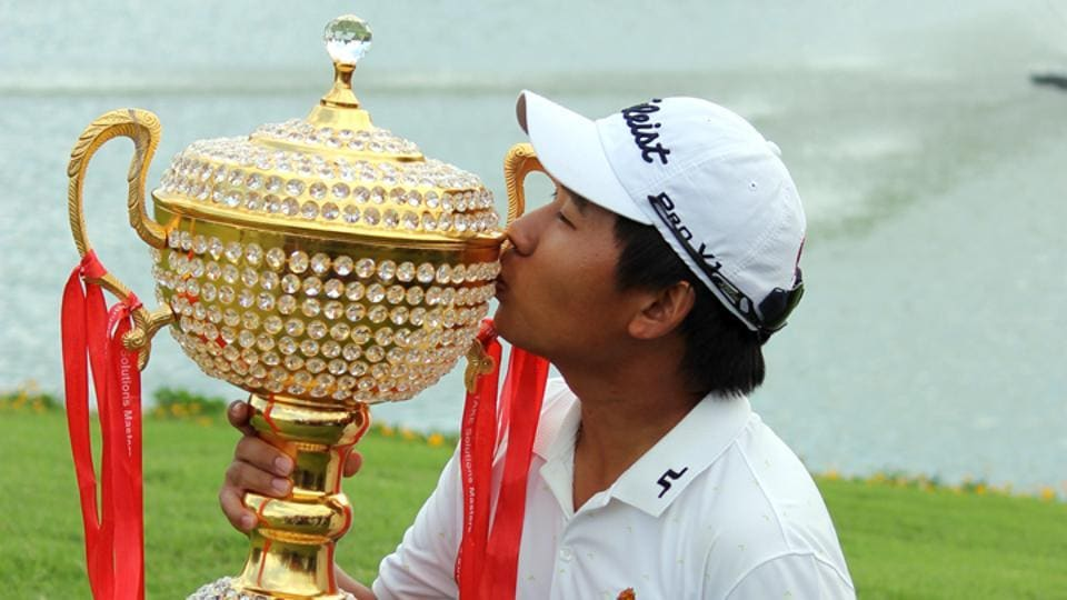 Poom Saksansin kisses the trophy after clinching the Take Solutions Masters golf title.