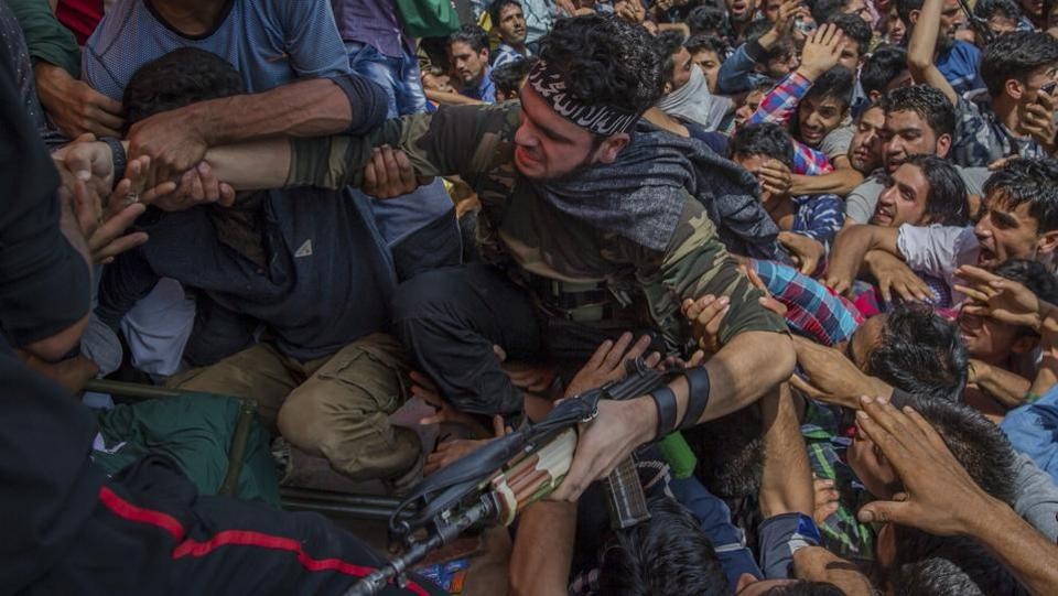 Villagers help a Kashmiri militant to climb on a stage as he appears at a funeral to pay tributes to slain rebel Suhail Ahmed, who was killed in an ambush by Indian government forces in Tantraypora, south of Srinagar. (Dar Yasin / AP)