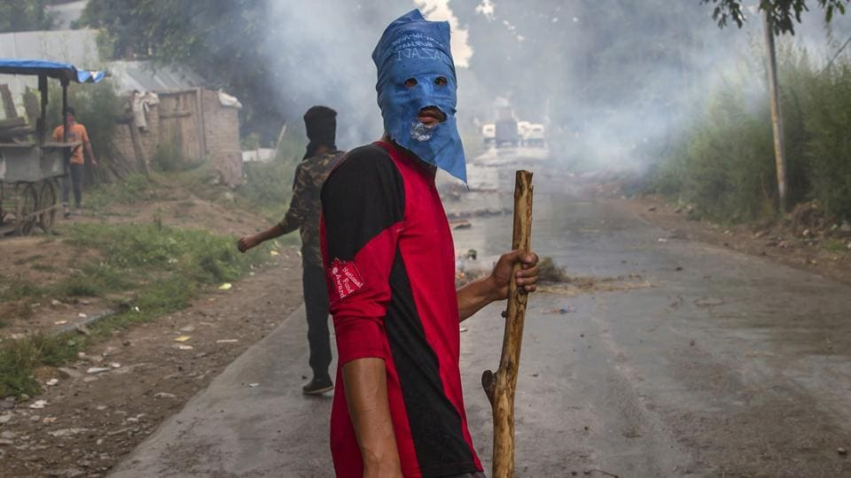 A masked villager holds a wooden stick and a stones during a protest following the funeral procession of Akeel Ahmed Bhat, a teenage boy in Haal village, about 47 Kilometers (29 miles) south of Srinagar. (Dar Yasin / AP)