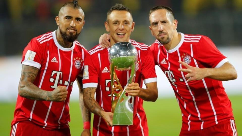 Bayern Munich's Arturo Vidal, Rafinha and Franck Ribery celebrate with the trophy after winning the DFL-Supercup Final.