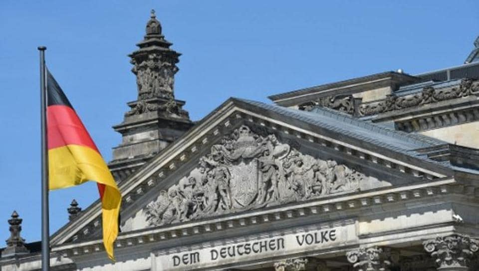 A German national flag is displayed in front of the main entrance of the Reichstag building, seat of the German lower house of parliament Bundestag, in Berlin.