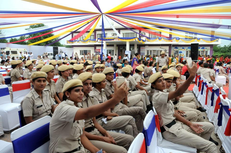 Women police personnel take selfies at a function organised to mark the second anniversary of the women's police station in