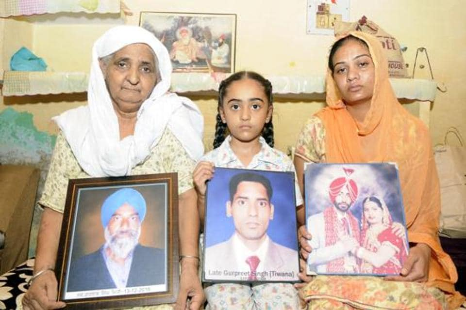 (From left) Jaspal Kaur, her granddaughter Amarpreet and daughter-in-law Rajbir Kaur holding photographs of their family members in Fatehgarh Sahib.