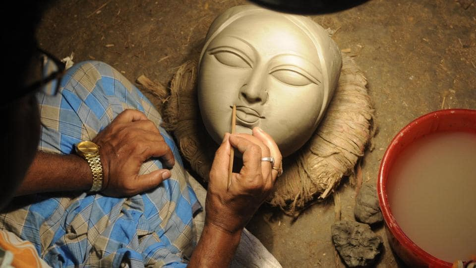 A clay idol maker is busy to finish face of Durga at Kumartuli, a hub of artists in Kolkata. (Samir Jana/HT PHOTO)