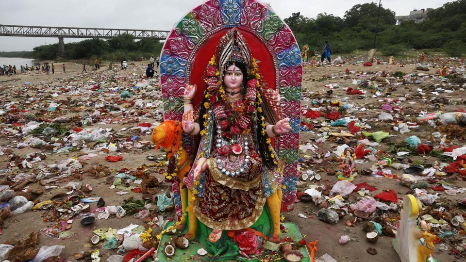 An idol of Hindu goddess Dashama stands among offerings and worship materials on the bank of river Sabarmati after the end of Dashama festival in Ahmadabad, India. (Ajit Solanki / AP)