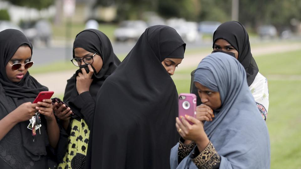 People make phone calls as law enforcement investigate an explosion at the Dar Al-Farooq Islamic Center in Bloomington on Saturday, August 5, 2017.