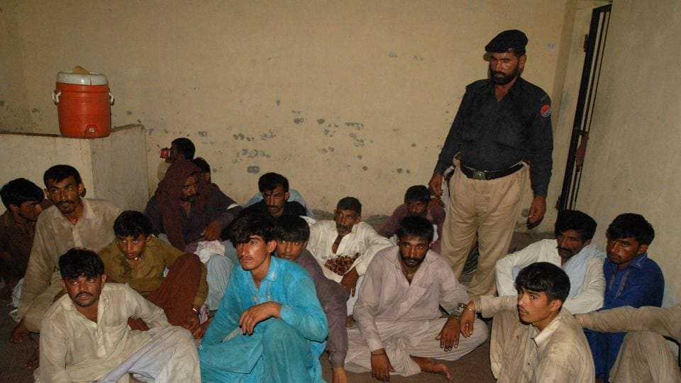 In this photo taken on July 27, 2017, a Pakistani policeman (R) stands beside arrested members of a village council, who ordered the rape of a teenage girl as punishment for a rape committed by her brother, at a police station in Raja Ram village on the outskirts of Multan.