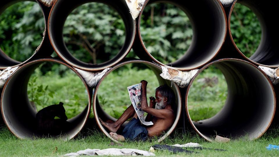 An Indian man reads a newspaper as he sits inside a pipe in New Delhi. (Money SHARMA/ AFP)