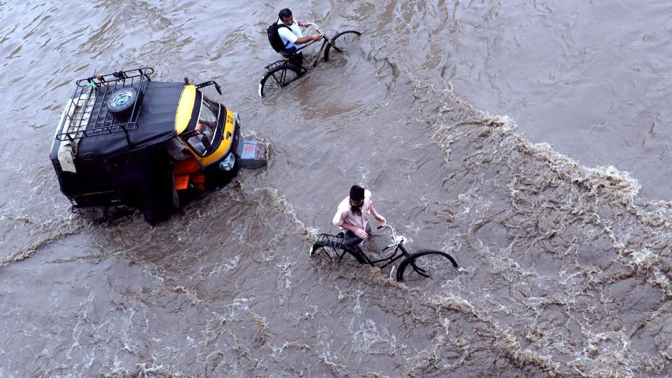 Cyclists wade next to an auto rickshaw along a flooded street after heavy rains in Patiala. (AFP)