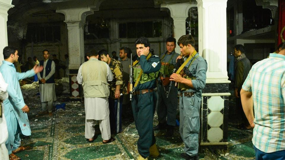 Afghan security personnel inspect the site of a suicide bomb attack at a Shiite mosque in Herat on August 1, 2017.