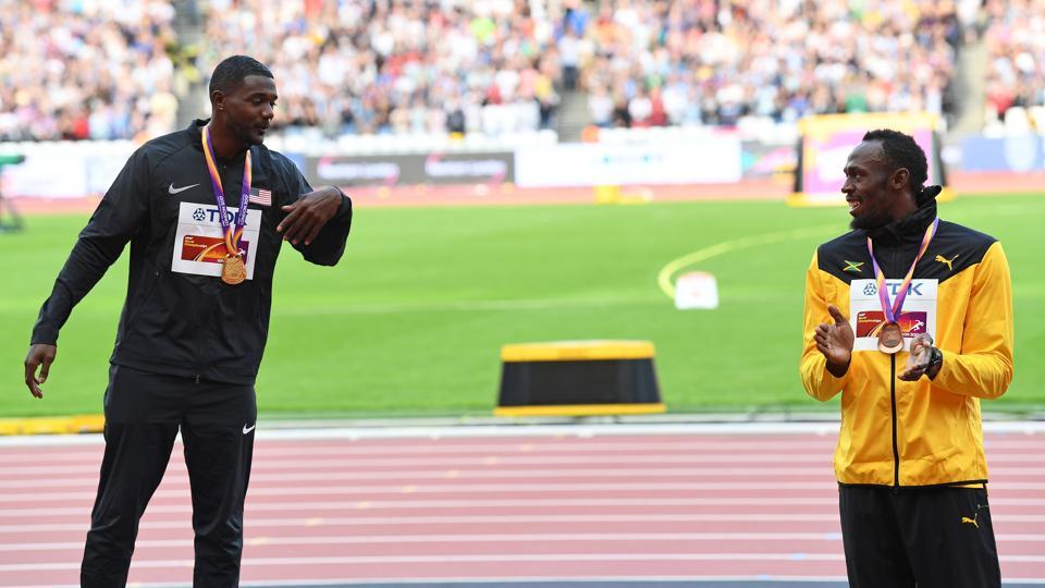 Justin Gatlin (L) invites Usain Bolt onto the top rung of the podium the victory ceremony of the men's 100m event at the IAAF World Championships of Athletics in London on Sunday. (AFP)