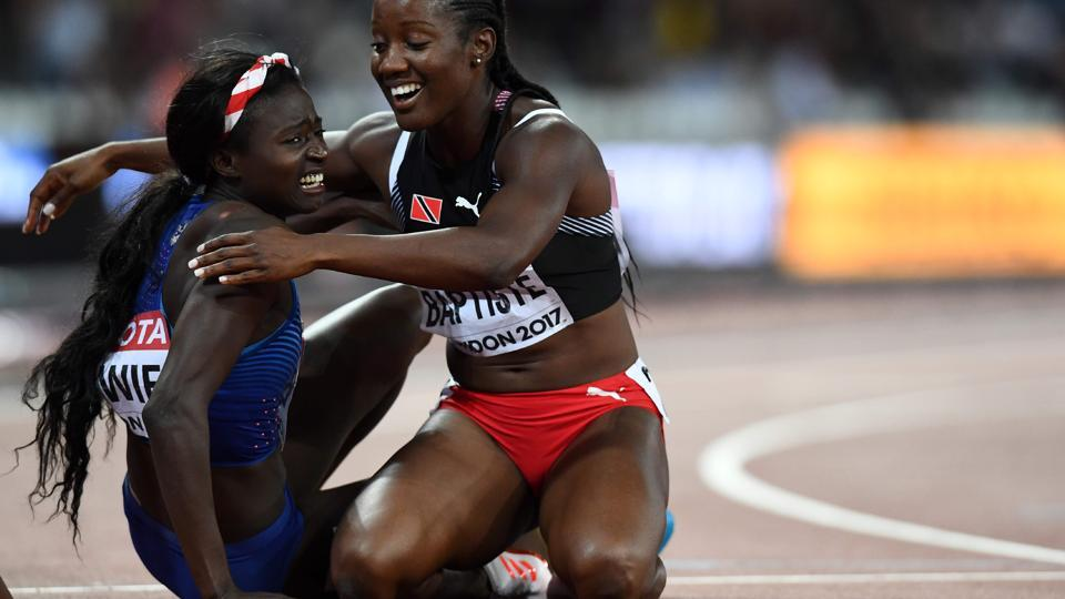 US athlete Tori Bowie (L) celebrates with Trinidad and Tobago's Kelly-Ann Baptiste after winning gold in the final of the women's 100m athletics event at the 2017 IAAF World Championships at the London Stadium in London on August 6, 2017. / AFP PHOTO / Jewel SAMAD