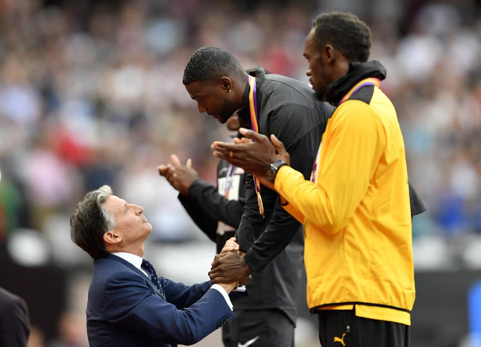 Gold medallist Justin Gatlin receives his prize from IAAF president Sebastian Coe as Usain Bolt cheers on during the podium ceremony of the men's 100m event at the IAAF World Championships of Athletics in London on Sunday (AP)