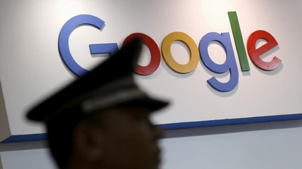 A security guard keeps watch as he walks past a logo of Google in Shanghai, China.