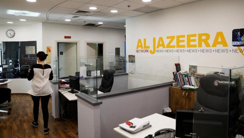 An employee walks inside an office of Qatar-based Al-Jazeera network in Jerusalem.