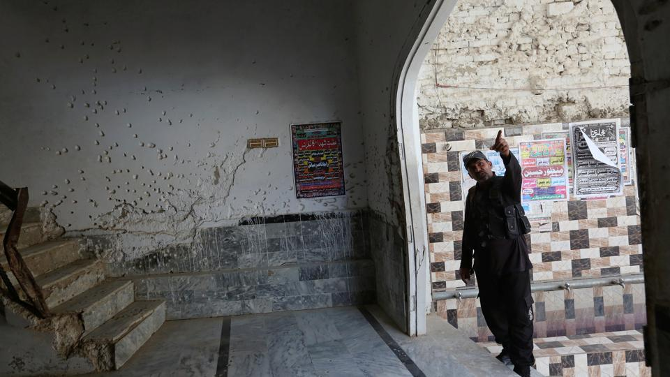 A policeman gestures beside a wall with shrapnel scars caused by a suicide blast at a Shi'ite mosque in Shikarpur, Pakistan.