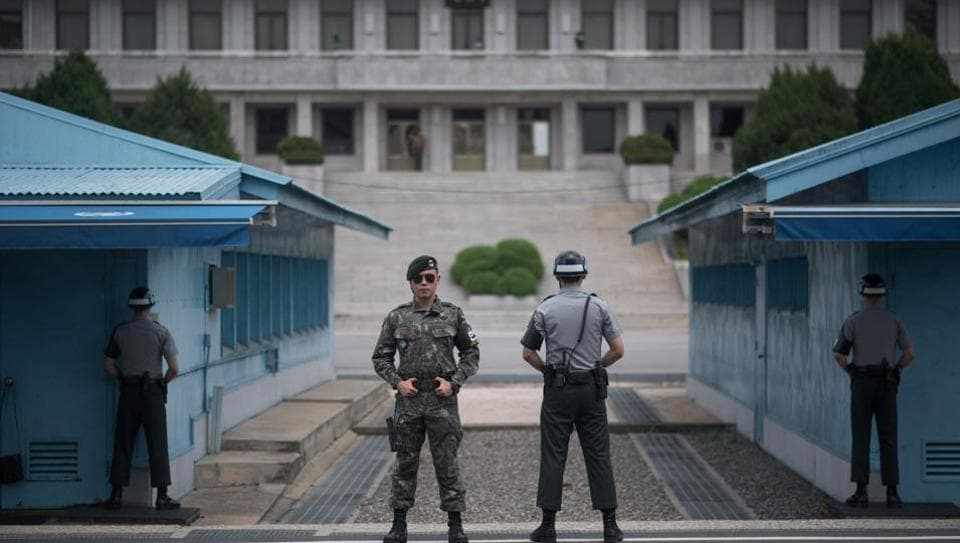 In a photo taken on August 2, 2017 South Korean soldiers stand guard before North Korea's Panmon Hall (rear C) and the military demarcation line separating North and South Korea, at Panmunjom, in the Joint Security Area (JSA) of the Demilitarized Zone (DMZ).