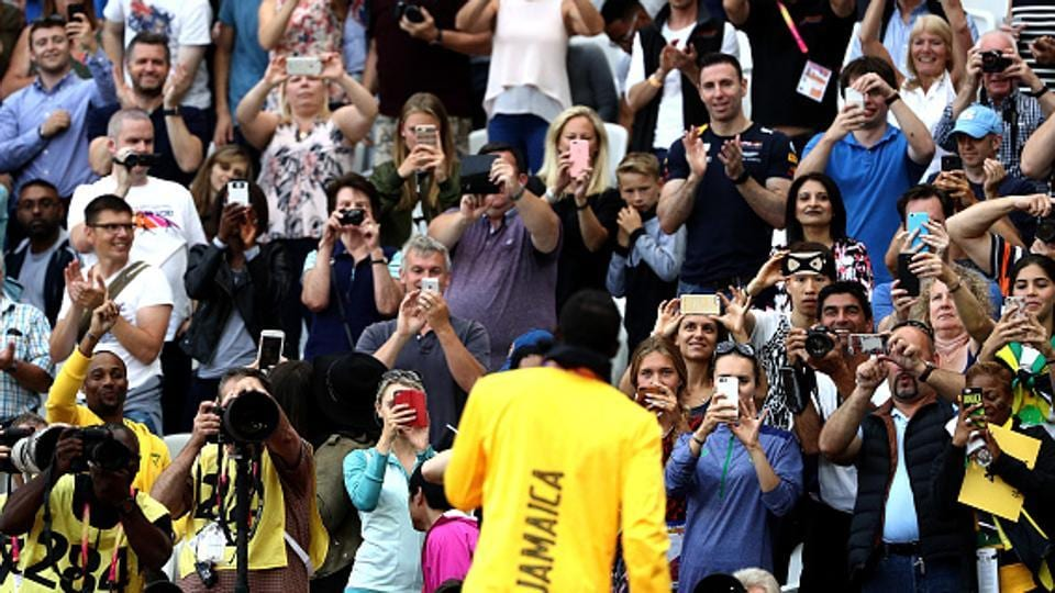 Usain Bolt obliges the photographers and the fans after the podium ceremony of the men's 100m event at the IAAF World Championships of Athletics in London on Sunday. (Getty Images)