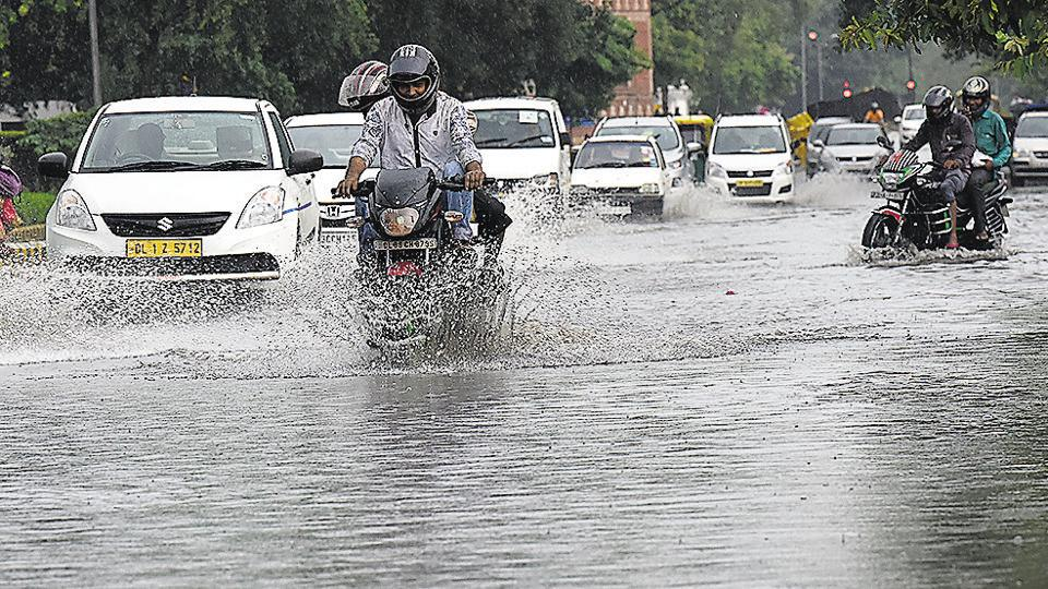 Vehicles drive through the water-logged Kharak Singh Marg  in New Delhi on Monday.