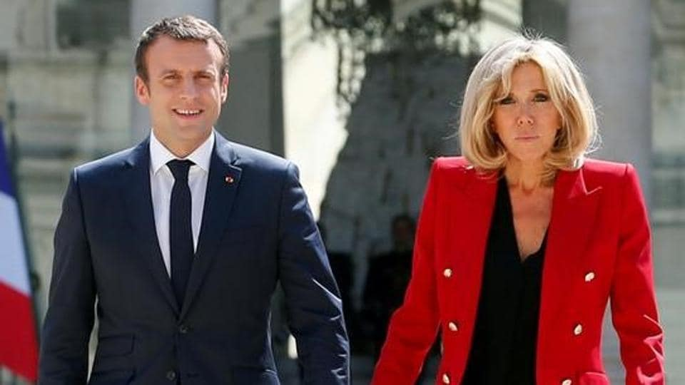 French President Emmanuel Macron and his wife Brigitte Macron walk in the Elysee Palace courtyard July 6, 2017.
