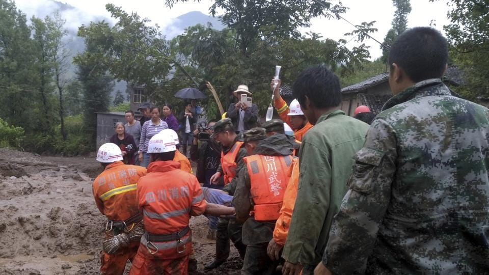 Rescuers carry a man injured in a landslide in Gengdi village in southwestern China's Sichuan province.