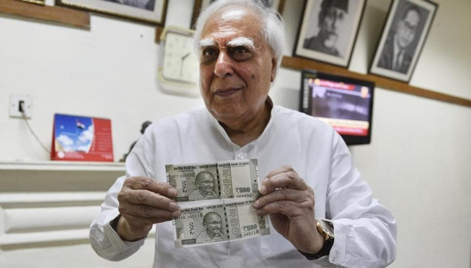 Congress leader Kapil Sibal shows the two kinds of Rs 500 notes in New Delhi on Tuesday.