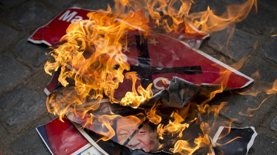 Activists of Swadeshi Jagaran Manch, a right wing organization that promotes indigenous products, burn portraits of Chinese President Xi Jinping during a protest in New Delhi.