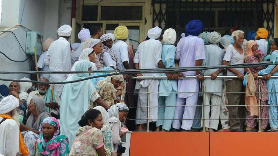 Villagers queue to receive their pension, outside a bank in Amritsar on July 27, 2017.