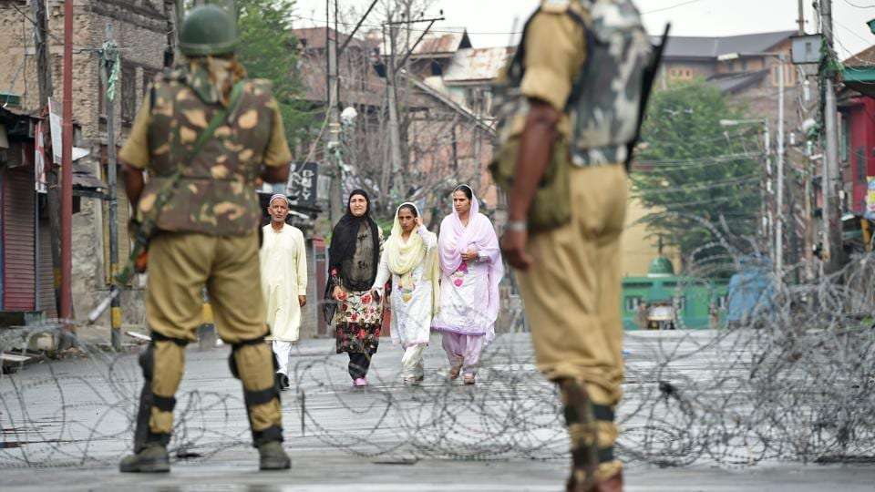 Paramilitary troopers stand guard as Kashmiri pedestrians walk along a road during restrictions n August 2, 2017.