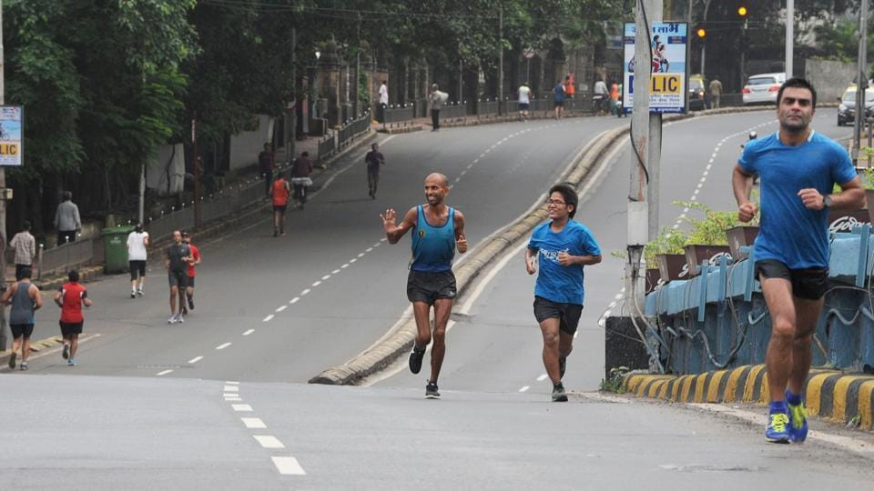 Runner Samir Singh (C) waves to other runners in Mumbai. Initially, friends mocked the man from Madhya Pradesh for taking on this challenge, but it became an attempt to show the endurance of human spirit that caught the public imagination. As word spread, fans joined Singh for several stretches of his run each day. (Indranil Mukherjee / AFP)