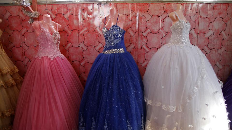 In this Sunday, Aug. 6, 2017 photo, bridal gowns and engagement dresses are displayed in a small shop in the Zaatari camp for Syrian refugees in northern Jordan.
